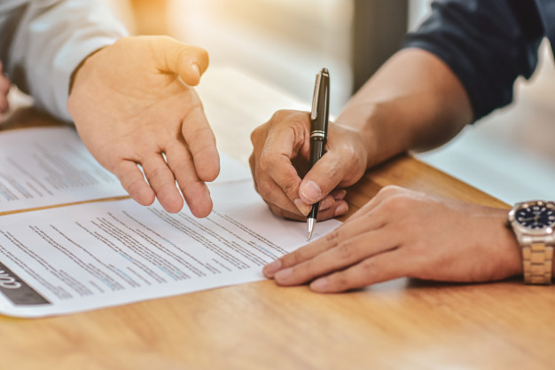 close-up-hand-holding-pen-sign-contract-document_10541-1024